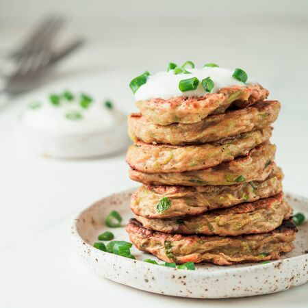 Zucchini fritters. Traditional zucchini fritters in stack on white background. Zucchini pancakes or fritters with green onion and parmesan cheese,served sour cream or greek yogurt. Copy space for text