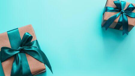 Dos cajas de regalo en papel de regalo artesanal y cinta de raso verde sobre fondo azul turquesa, copie el espacio en el centro. Hermosos regalos de Navidad, año nuevo o cumpleaños, vista plana o superior. Bandera