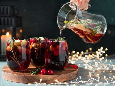 Female hand pours winter sangria in glasses with fruit slice, cranberry and rosemary. Dark christmas holiday background with candle, decoration lighting chain. 스톡 콘텐츠 - 133236201