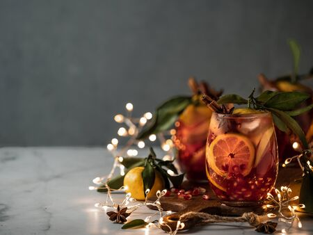 Winter sangria on dark christmas holiday background. Jugful of sangria and glasses with fruit slice, cranberry and rosemary. Copy space for text or design. Horizontal. Decoration lighting chain. 스톡 콘텐츠