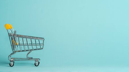 Shopping cart on blue background. Shop trolley at supermarket as sale, discount, shopaholism concept with copy space for text or design. Reklamní fotografie