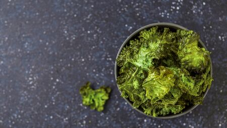 Green Kale Chips with salt in bowl. Homemade healthy snack for low carb, keto, low calorie diet. Dark blue background. Ready-to-eat kale chips, copy space for text. Top view or flat lay. Banner