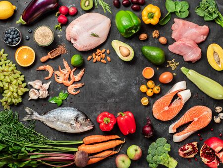 Pegan diet conept with copy space in center. Vegan plus paleo diet food ingredients - vegetables, fruits, raw meat and fish on dark background. Top view or flat lay Reklamní fotografie