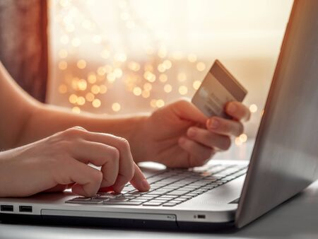 Cristmas online shopping soncept. Close-up womans hands holding credit card and inputting card information using laptop keyboard for online shopping with festive lighting chain bokeh.