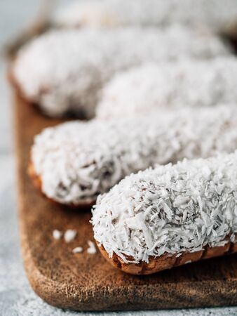 Homemade eclairs with coconut on wooden cutting board. Close up view of delicious healthy profitroles with shredded coconut. Copy space for text or design. Vertical.