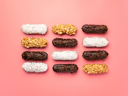 Set of different homemade eclairs on pink background. Top view of delicious healthy profitroles with different decor - chocolate, peanut and sherdded coconut