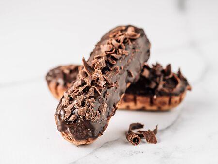 Eclairs caseros con chocolate sobre fondo de mármol blanco. Vista cercana de deliciosos profitroles saludables con glaseado de chocolate