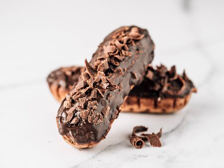 Homemade eclairs with chocolate on white marble background. Close up view of delicious healthy profitroles with chocolate glaze
