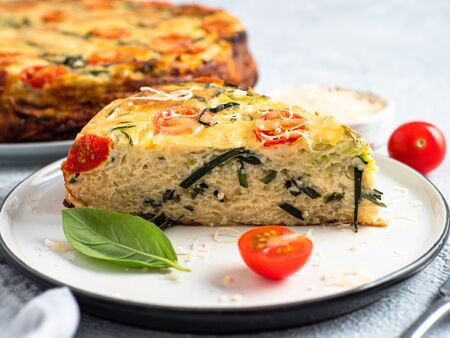 Zucchini pie and ingredients on gray background, copy space. Piece of delicious savory pie with zucchini, tomatoes, herbs and cheese. Idea and recipe for healthy baking and lot to harvest of zucchini
