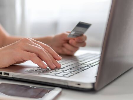 Online shopping concept. Close-up womans hands holding credit card and using laptop keyboard for online shopping