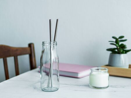 Metal drinking straws in glass bottle on white marble table indoor. Metal straws on table in living room interior. Recyclable straws, zero waste concept.