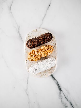 Set of three homemade eclairs on marble background. Top view of delicious healthy profitroles with different decor elements - chocolate, peanut and sherdded coconut. Vertical Reklamní fotografie