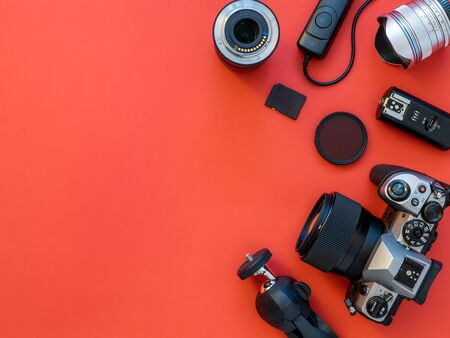 Photographer workplace with dslr camera, lens, pen tablet and camera accessories on red background. Camera, photography, visual content concept. Flat lay or top view. Copy space for text or design 版權商用圖片
