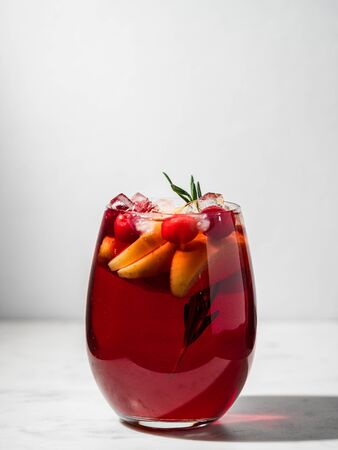Winter sangria on tabletop. Glasses of sangria with fruit slice, cranberry and rosemary. Vertical. Copy space for text or design.