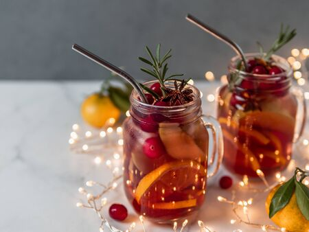 Winter sangria in mason jars with metal straws on christmas holiday background. Decorated fruit slice, cranberry and rosemary. Copy space for text or design. Horizontal. Decoration lighting chain Stock Photo
