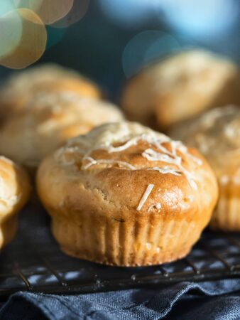 Delicious savory salted muffins with cream cheese, herbs and spices, topping grated parmesan. Close up view, selective focus.
