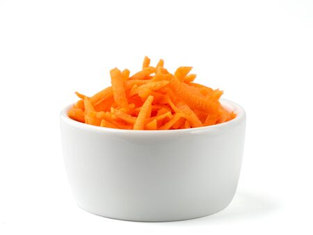 Fresh organic shredded carrots in small white bowl. Raw grated carrots isolated on white with clipping path.
