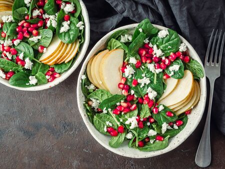Vegan salad bowl with arugula, pear, pomegranate, cheese on black background. Vegan breakfast, vegetarian food, diet concept. Top view or flat lay. Copy space for text.