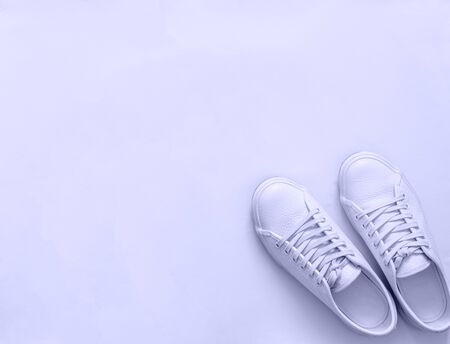 White leather sneakers on white background. Pair of fashion trendy white sport shoes or sneakers with copy space for text or design. Overhead shot of new white sneakers,monochrome.Top view or flat lay 版權商用圖片