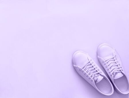 Violet leather sneakers on violet background. Pair of violet sport shoes or sneakers with copy space for text or design. Overhead shot of new violet sneakers,monochrome. Top view or flat lay
