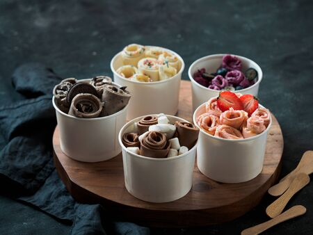 Rolled ice cream in cone cups on rustic round wooden tray. Different thai style rolled ice cream on datk background