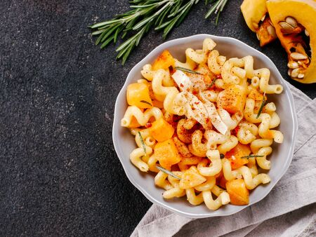 Fusilli pasta with pumpkin, rosemary and brie cheese. Idea recipe pasta. Vegetarian food. Homemade pasta dish in gray bowl over black concrete background. Copy space. Top view or flat lay.