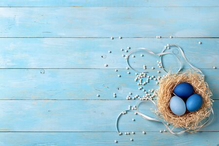 Easter concept. Ombre eggs in blue colors on blue wooden background with copy space for text. Top down view or flat lay. Classic blue colors in Easter 2020