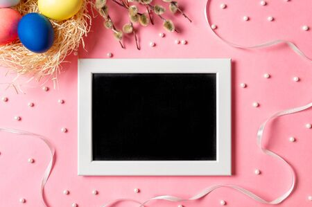 Orthodox Easter concept. Colorful eggs and pussy willow branches on pink background with empty chalkboard. Copy space for greetings, text or design. Top down view or flat lay