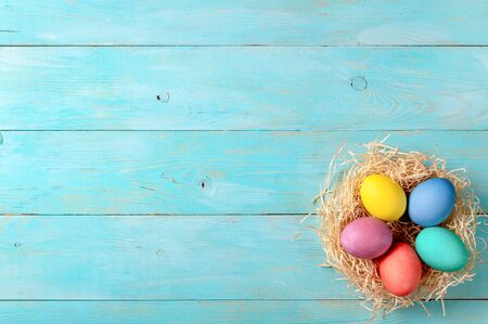 Easter concept. Colorful eggs on blue wooden background with copy space for text. Top down view or flat lay