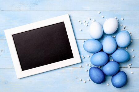 Easter concept. Ombre eggs in blue colors on blue wooden background with empty chalkboard. Top down view or flat lay. Classic blue colors in Easter 2020. Copy space for text Stok Fotoğraf