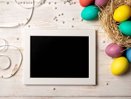 Easter concept. Colorful eggs on white wooden background with empty chalkboard. Copy space for greetings, text or design. Top down view or flat lay