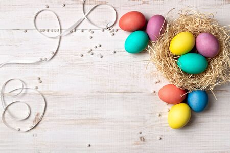Easter concept. Colorful eggs on white wooden background with copy space for text or design. Top down view or flat lay Stok Fotoğraf - 140186833