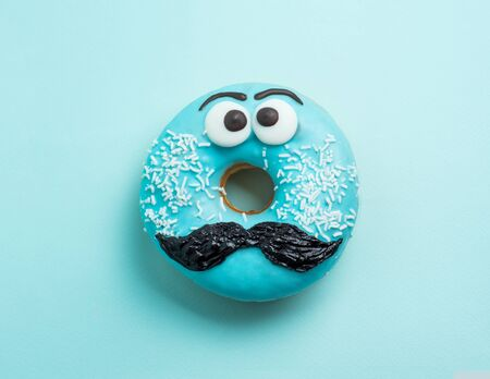 Blue glazed donut with mustache. Blue doughnut with funny face with mustache on blue background. Copy space for text. Masculinity or father day concept. Top view or flat lay