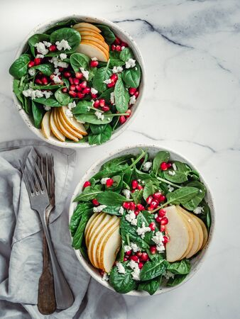 Vegan salad bowl with spinach, pear, pomegranate, cheese on marble tabletop. Vegan breakfast, vegetarian food, diet concept. Vertical. Top view or flat lay.