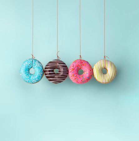 Four donuts hanging on the ropes. Harm of sugar, donuts time or healthy diet concept. Dependence on flavoring, diabetes problems, weight loss. Square shape. Copy space bottom