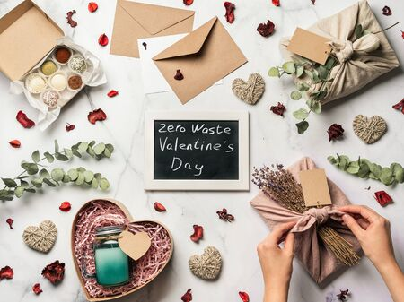 Zero waste Valentines Day concept. Eco-friendly gift cloth wrapping in Furoshiki style, homemade sweets and candle as gift ideas and chalkboard with Zero Waste Valentines Day letters on marble table