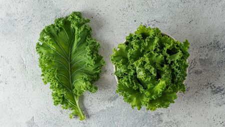 Fresh green kale leaf and salad on gray cement background, top view. Healthy detox vegetables. Clean eating and dieting concept. Flat lay. Health kale benefits
