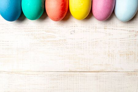 Easter concept. Colorful eggs on white wooden background with copy space for text. Top down view or flat lay 写真素材