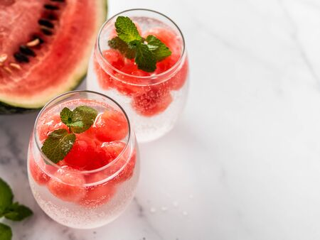 Watermelon ice with sparkling water or soda in glass tumbler. Summer party idea and recipe, add color and flavor for soda or other drink. Copy space. White marble background 写真素材