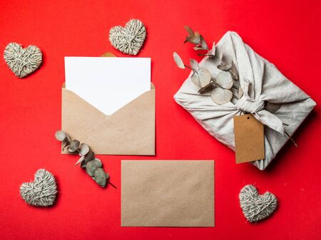 Zero waste Valentines Day concept and mock up on red. Eco-friendly gift cloth wrapping in Furoshiki style, craft paper envelope,empty greetings card. Top down view or flat lay. Copy space for design