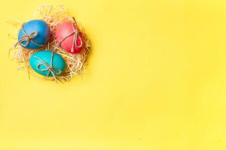 Easter concept. Colorful eggs on bright yellow background with copy space for text. Top down view or flat lay