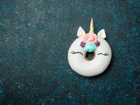 Unicorn donut over dark background. Trendy donut unicorn with white glaze. Top view or flat lay. Copy space for text.