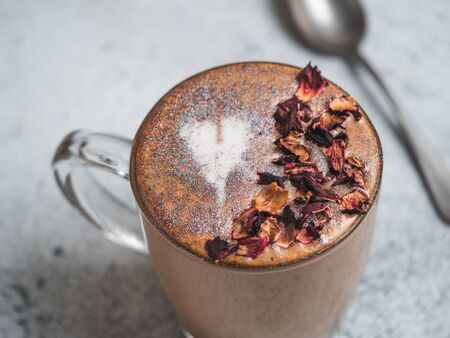 Trendy Coffee with edible glitter and dried rose petals. Cup of sparkly coffee or diamond cappuccino on gray table. Copy space for text