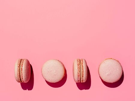 Pink macarons with copy space. Row of perfect french macarons or macaroons on pink background. Top view or flat lay. Hard light 写真素材