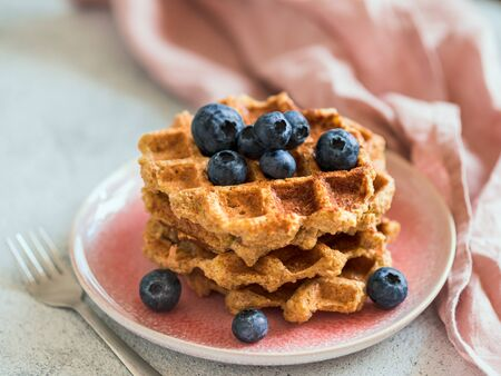 Easy healthy gluten free oat waffles with copy space. Stack of appetizing homemade waffles with oat flour decorated blueberries, on plate over light gray cement background