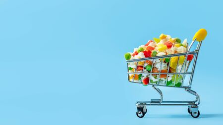 Frozen vegetables assorted in toy shopping cart on blue background. Full of assorted frozen vegetables food shop trolley. Banner with copy space left