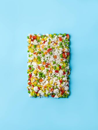 Frozen vegetables assorted on blue background. Assorted frozen vegetables food with ice, top view or flat lay. Raw uncooked frozen hawaii mix. Vertical. Stockfoto