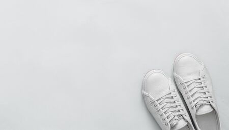White leather sneakers on blue background. Pair of fashion trendy white sport shoes or sneakers with copy space for text or design. Overhead shot of new white sneakers. Top view or flat lay. Banner