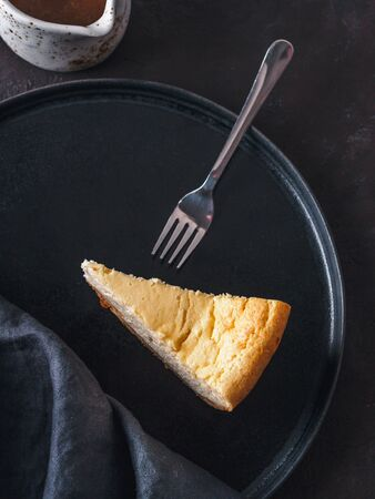 Plate with piece of cheesecake on dark background. Classic cheesecake, caramel sauce and dessert forks. Vertical. Top view or flat lay.