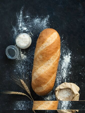 British White Bloomer or European sourdough Baton loaf bread on black background. Fresh loaf bread and glass jar with sourdough starter, floer in paper bag and ears. Top view. Copy space. Vertical. Stok Fotoğraf